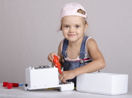 Girl repairs screwdriver toy microwave photo