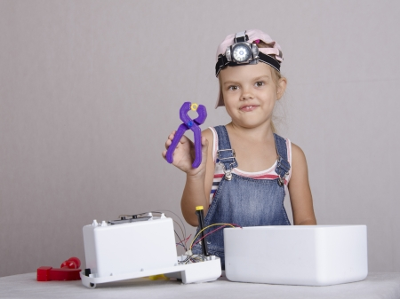 Girl repairs toy appliances photo