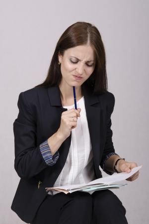 School teacher checks notebooks students with homework