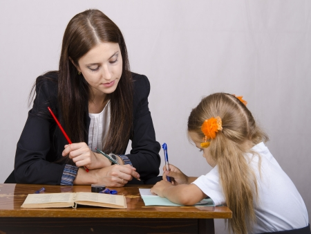 teaches: The teacher teaches lessons with a student sitting at the table