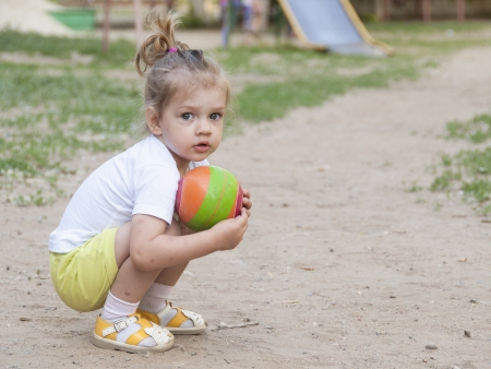squat: Little girl sitting on his haunches with a ball on the Playground Stock Photo