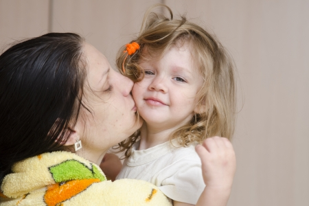 awakened: Mom hugs and kisses awakened fuzzy-looking child