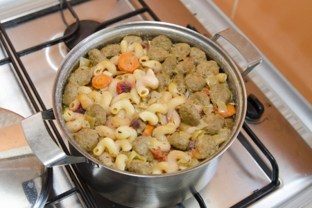 inability: Saucepan digested soup and swollen pasta stands on a gas stove