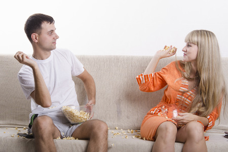 threw: Young couple sitting on the couch, and threw each other popcorn Stock Photo