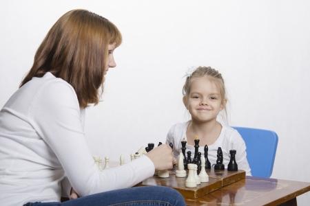 Mother explains daughter purpose of the chess pieces Banco de Imagens