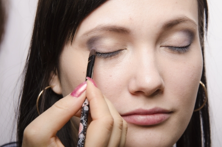 eyelids: Makeup artist in the process of makeup colors upper eyelids model Stock Photo