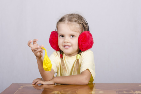 mystique: A child of four years in the headphones and with сдутым yellow ball is sitting at the table