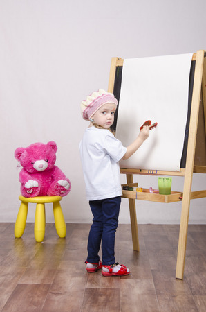 Three-year-old girl playing in the artist. Girl draws on the easel paints bear sitting on a chair