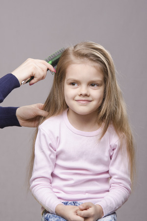Hairdresser brushing her long hair five year old girl photo