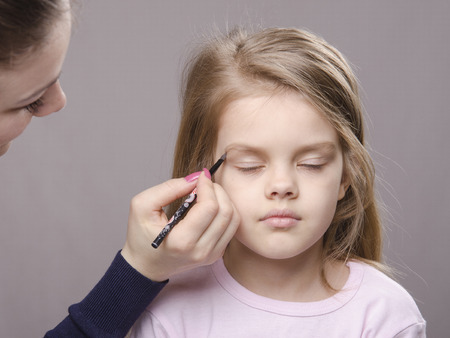sums: Makeup artist in the process of makeup brings eyebrows on the face five year old girl