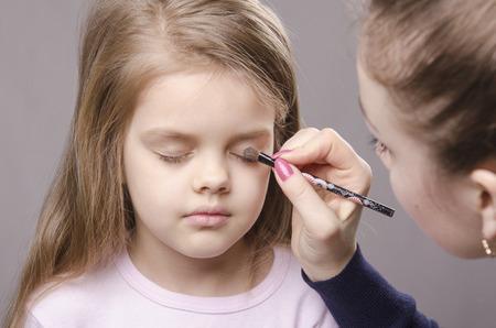 parpados: Artista de maquillaje en el proceso de maquillaje de los colores de los p�rpados en la cara de cinco a�os ni�a