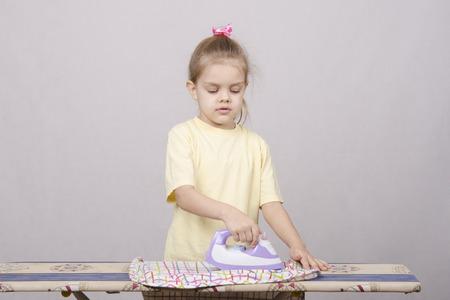 okşayarak: Beş yaşındaki kız, bir ev hanımı oynayan, ve şeyler demir okşayarak Stok Fotoğraf