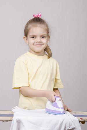 okşayarak: Beş yaşında bir kız bir ev hanımı oynayan ve işler demir okşayarak