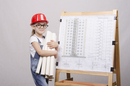 architect drawing: Girl Builder, architect, holding a bunch of drawings, standing at the blackboard with the drawing of the building