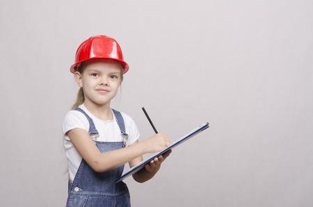 merchandiser: Girl engineer is a helmet folder and writes in folder