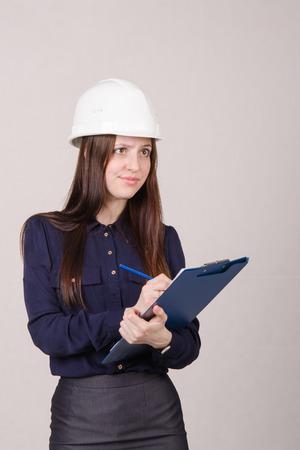 merchandiser: Young woman builder in helmet standing with a folder in hand Stock Photo