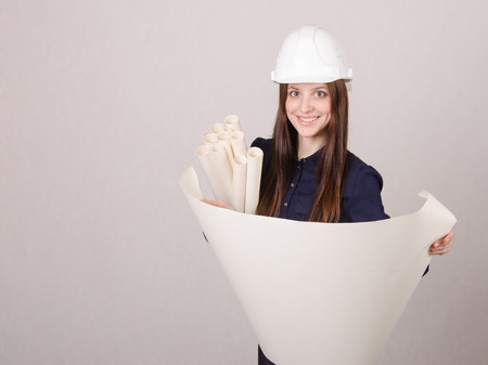 deployed: Young woman architect in hardhat standing with blueprints in hand