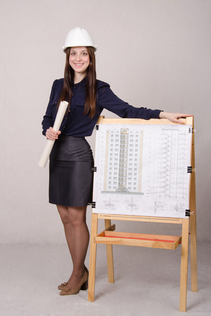 A young girl stands at the blackboard drawing multistory apartment house, in the hands of a few drawings it