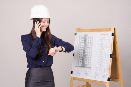 architect drawing: Young woman architect standing at drawing board mounted on the project of a multistory building