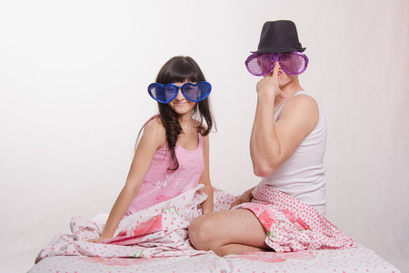 Young couple sitting in bed and each wore big glasses photo