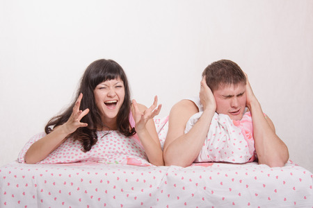 Young family couple quarrels in a bed