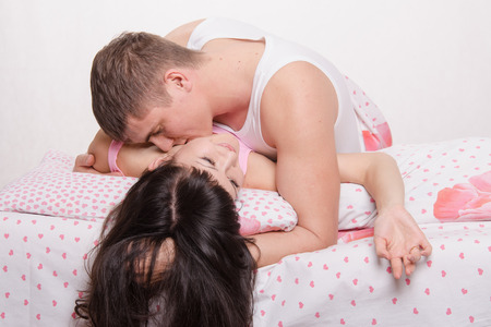 Young beautiful couple kissing and embracing in bed photo