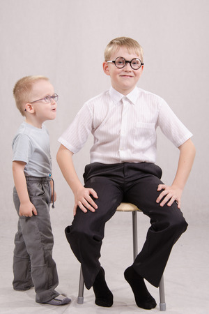 five to twelve: Twelve year old boy with glasses sitting on a chair, standing next to a year-old boy