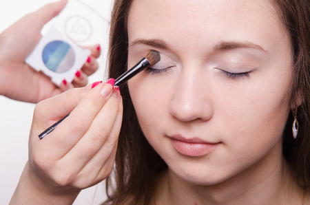 eyelids: Makeup artist paints the eyelids of a beautiful young girl in the makeup Stock Photo