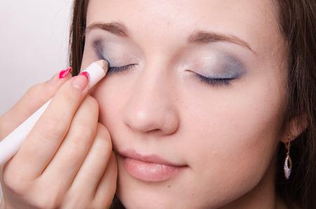 parpados: Artista de maquillaje pinta los p�rpados de una chica joven y bella en el maquillaje