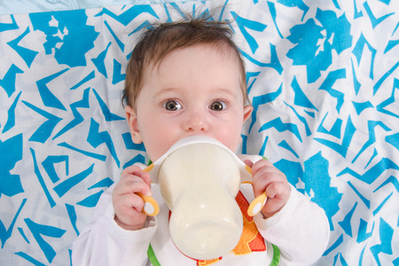 Six month old baby drinking milk from a bottle with the teat Stock Photo