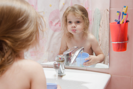 puffed cheeks: three year old girl to rinse your mouth after brushing your teeth in the bathroom
