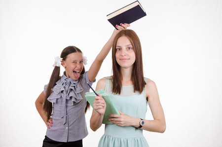 unsatisfactory: Trainee teacher mocks trying to hit her over the head with a book Stock Photo