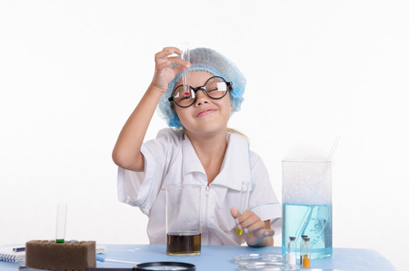 simplest: Girl sitting in chemistry class and makes the simplest experiments