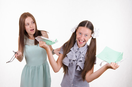 mocks: Schoolgirl having fun tearing the notebook in front of an angry teacher