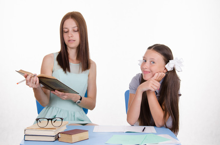 teaches: Teacher teaches the student sitting with him at the table Stock Photo