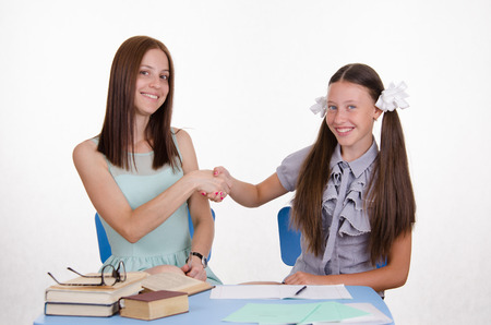 teaches: The teacher teaches the student sitting with him at the table