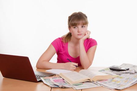 encyclopedias: Una joven se sienta en una mesa con un mont�n de peri�dicos, enciclopedias y un ordenador port�til Foto de archivo