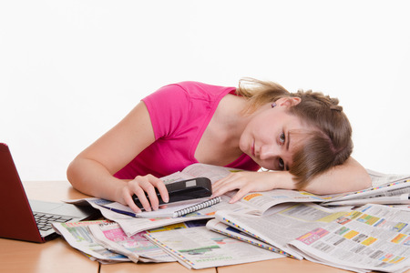 A young girl sits at a table with a pile of newspapers, encyclopedias and a laptop