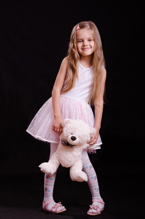 five year old: Portrait of a beautiful five year old girl with a teddy bear on a black background