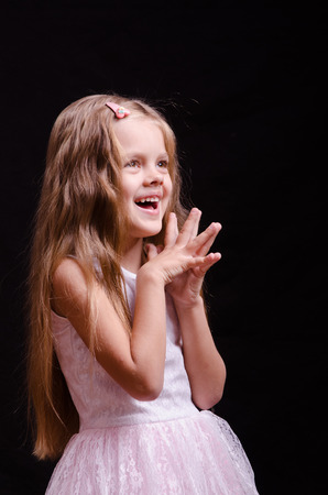 treasured: Portrait of a beautiful five year old girl on a black background