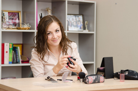 Young woman sitting at office table, laid out on the table cosmetics