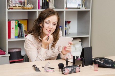 colours tints: A young girl puts makeup in the office workplace