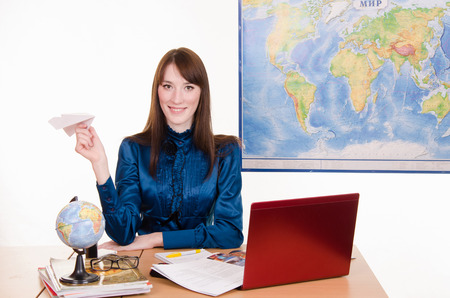 selling service smile: Young beautiful employee in the office of the travel agency Stock Photo