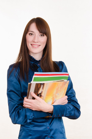 Portrait of a young beautiful girl in a strict office clothes and magazines in the hands of photo