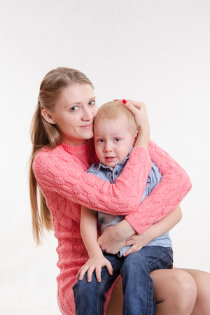three year old: On the lap of a young beautiful girl sits her three year old son
