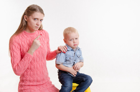 Young beautiful mother scolds her rebellious and moody three year old boy Foto de archivo
