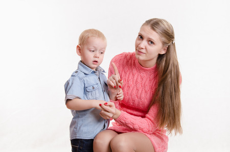 three year old: Young beautiful mother scolds her rebellious and moody three year old boy Stock Photo