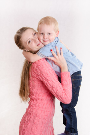 Young beautiful girl hugging her three year old son