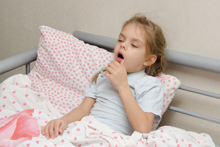 cough: Six year old girl coughs diseased lying in bed with a thermometer on the mouse