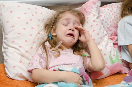 bad mood: The three-year diseased girl lying in bed, Meria temperature thermometer, in a bad mood Stock Photo